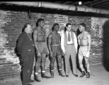 Three boxers and two trainers looking at each other